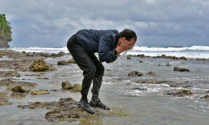 Presiden Jokowi saat membasuh wajahnya dengan air laut di pantai Talaud, Sulut